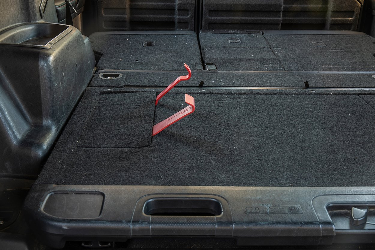 Remove rear cargo tray bolt covers